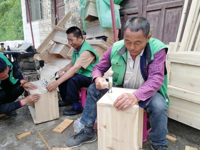 图为在基地就业的两位残疾人在为蜂箱钉钉子.jpeg